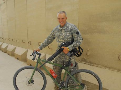 Gussman standing with bike in military uniform
