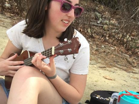A person holding a ukulele and sitting on the ground