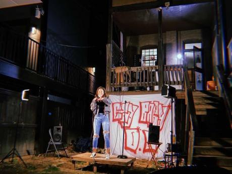 Woman at a microphone in a row house backyard at night